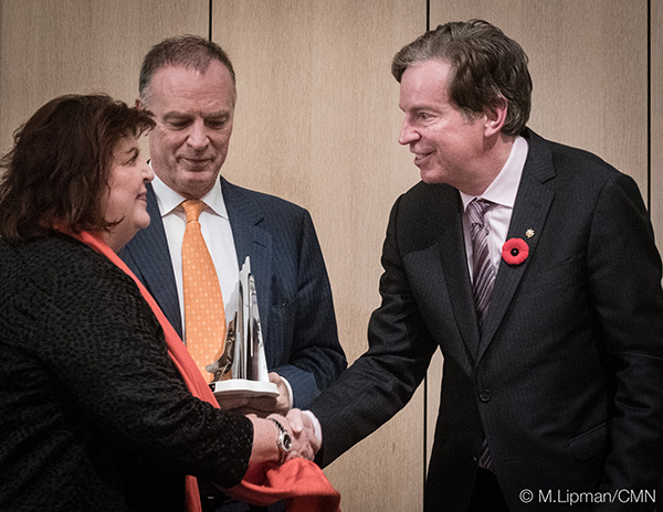 Un homme serre la main d'une femme qui reçoit un prix.