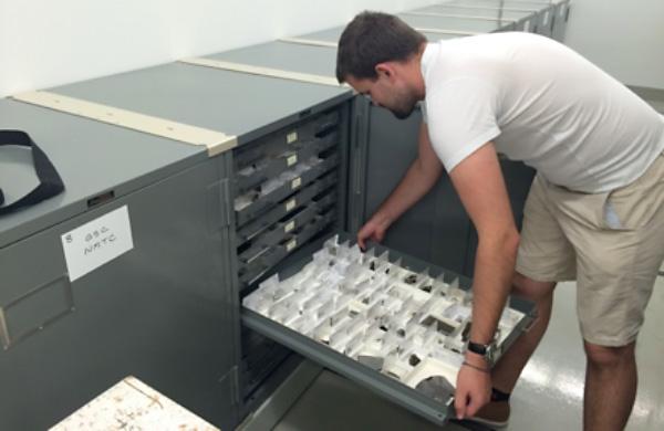Un homme insère un tiroir d'échantillons dans une armoire.