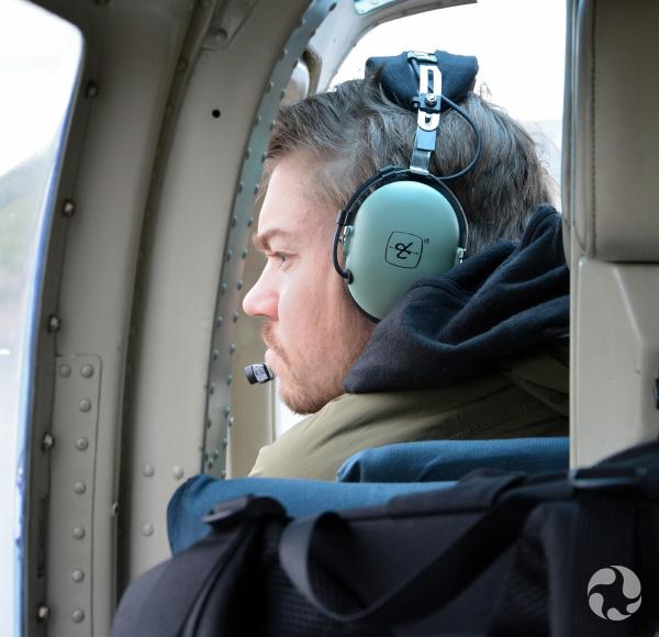 Un homme assis dans un hélicoptère regarde dehors.