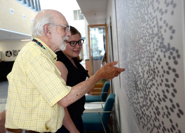 Un chercheur et un étudiant regardent la murale
