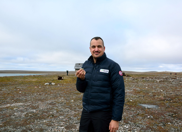 Un homme debout dans la toundra au Nunavut avec un lichen dans la main.