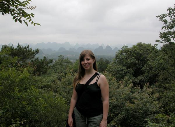 Une femme debout devant des arbustes, à Guangxi, en Chine.