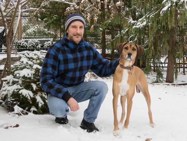 Un homme portant une veste à carreaux bleus et noirs, accroupi dans la neige avec son chien.
