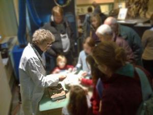 Une femme debout devant une table sur laquelle reposent des fossiles; elle parle avec des visiteurs du Musée.