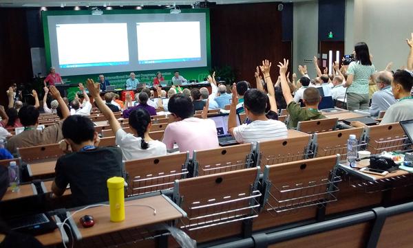 Quatre personnes s'adressant à une salle comble. L'assistance vote sur les questions qui lui sont présentées en levant la main.