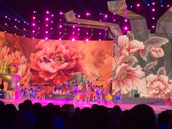 Des danseurs évoluent sur la scène devant d'immenses représentations de plantes.