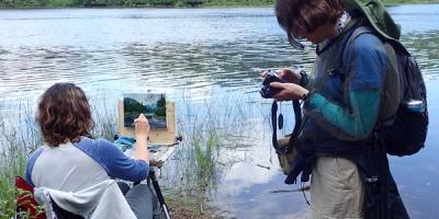 Une scène dans la forêt : une femme peint pendant qu'une autre, à sa droite, examine les photos sur son appareil.