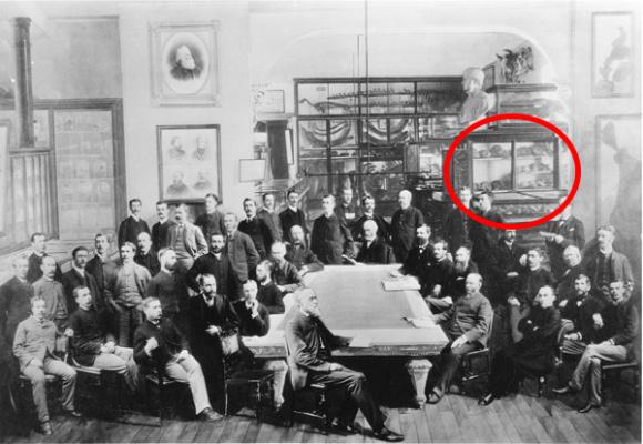 Des hommes assis autour d'une table avec une exposition à l'arrière-plan.