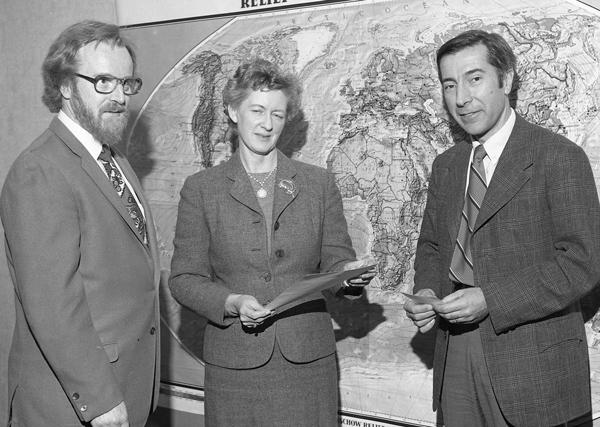 Frances Wagner, tenant un morceau de papier, entre deux hommes