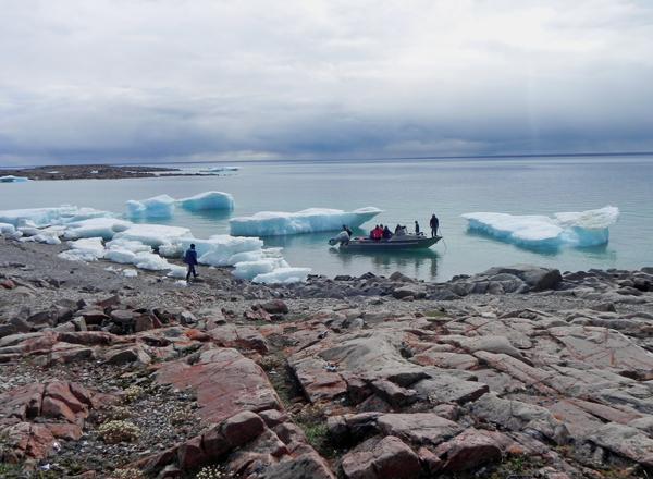 Des gens en bateau abordant un rivage arctique.