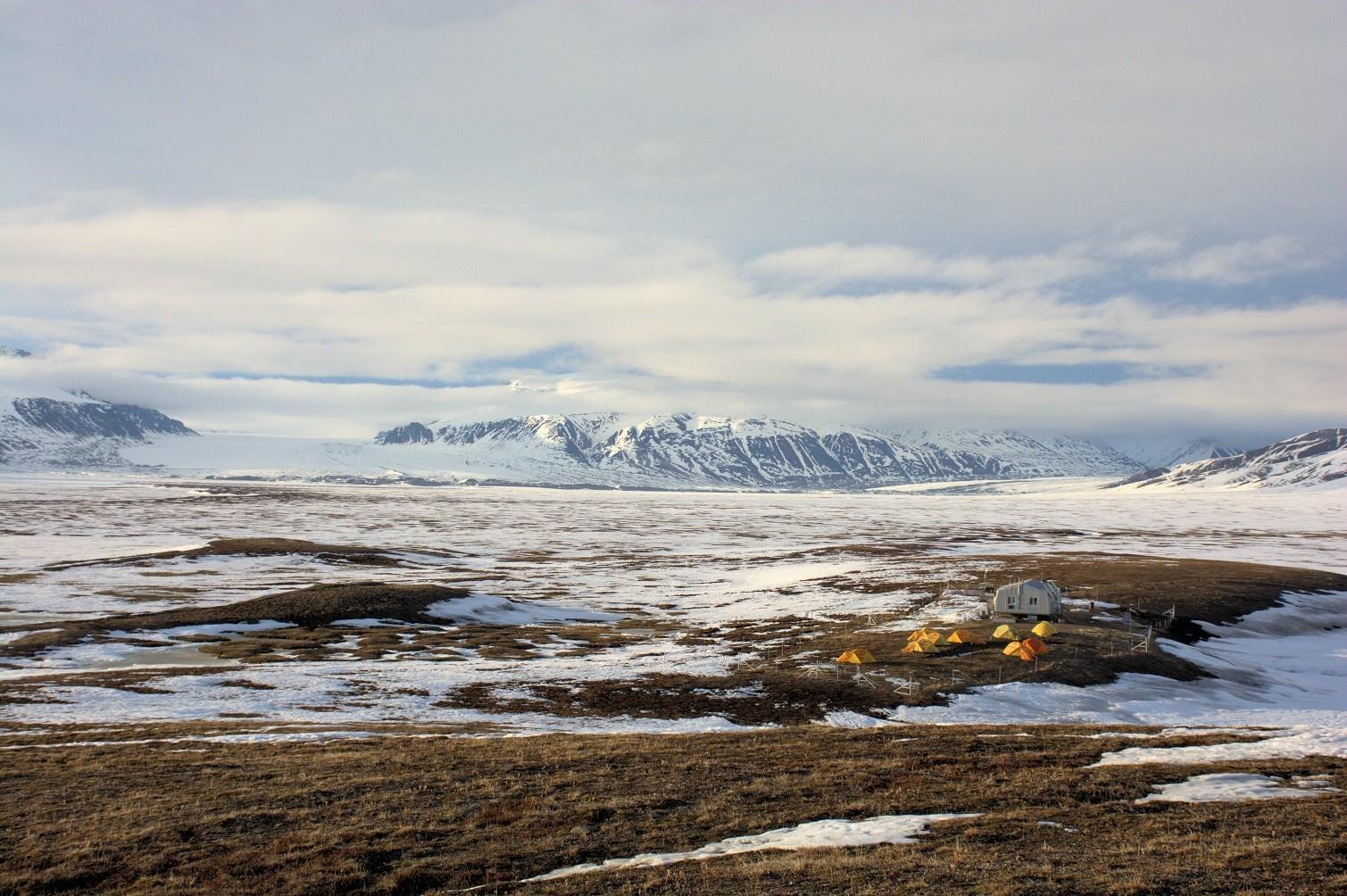 Paysage arctique montrant un camp de recherche et des montagnes en arrière-plan