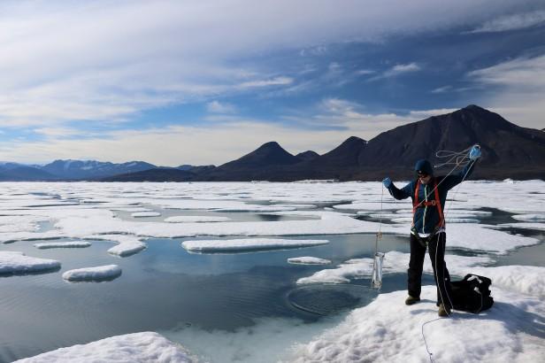 Un homme sur la glace au bord d'un lac partiellement gelé, sur fond montagneux, prélève un échantillon dans un tube retenu par une longue corde.