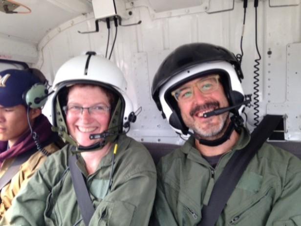 Photo de deux personnes à bord d'un hélicoptère.