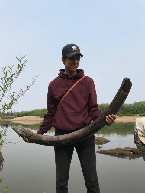 Photo d'un jeune homme tenant une défense de mammouth.