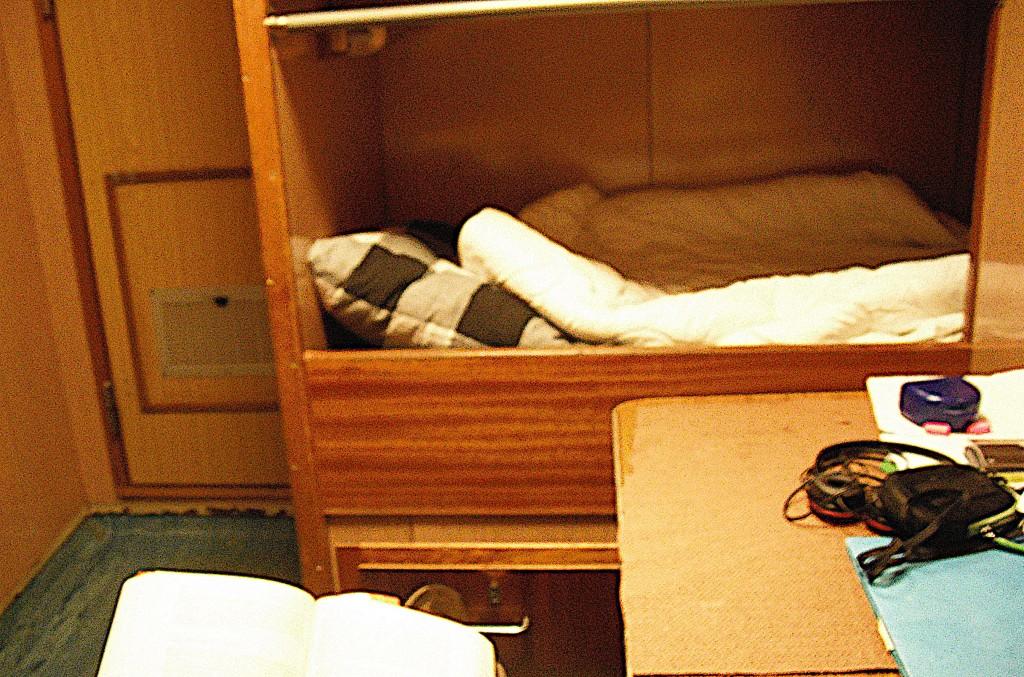 Une couchette de bois ouverte, assortie d'un matelas et d'un oreiller.