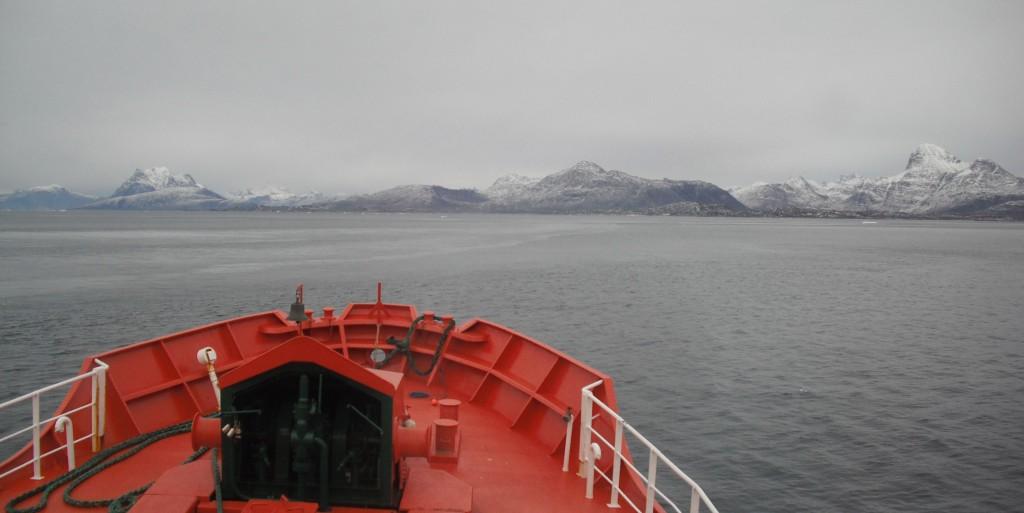 Au premier plan, la proue d'un navire. Derrière, l'océan gris et des montagnes aux sommets enneigés.
