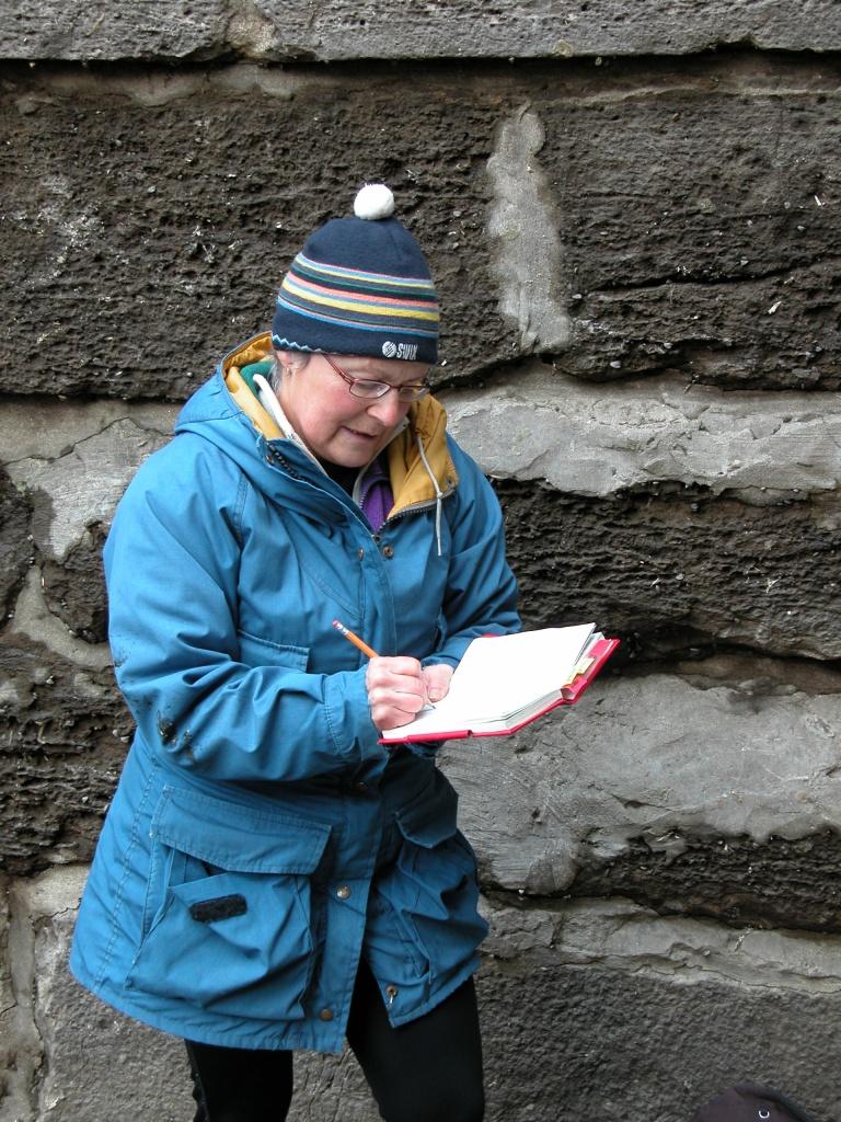 Devant un mur de briques, une femme en vêtements d'hiver écrit dans un cahier rouge.