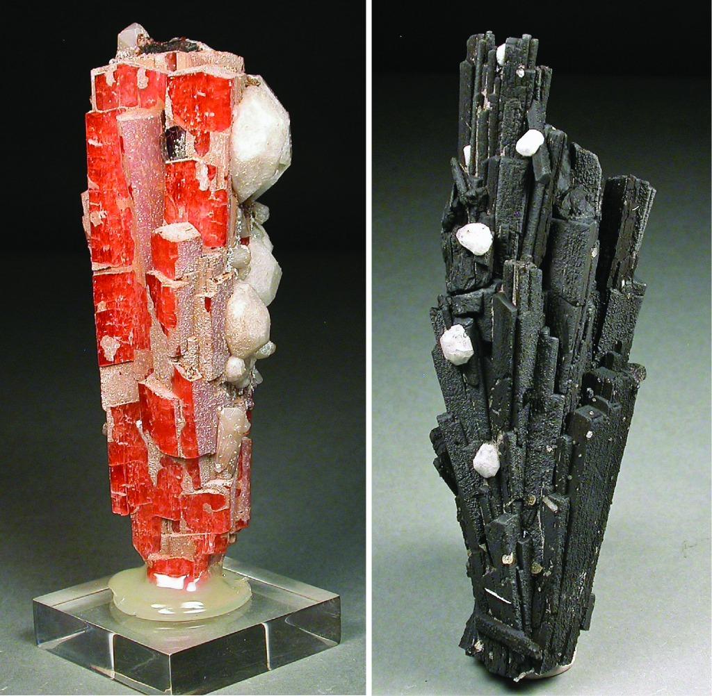 Deux spécimens. À gauche, un groupe de cristaux prismatiques presque parallèles de sérandite orange; à droite, un groupe de cristaux noirs ayant une forme similaire.