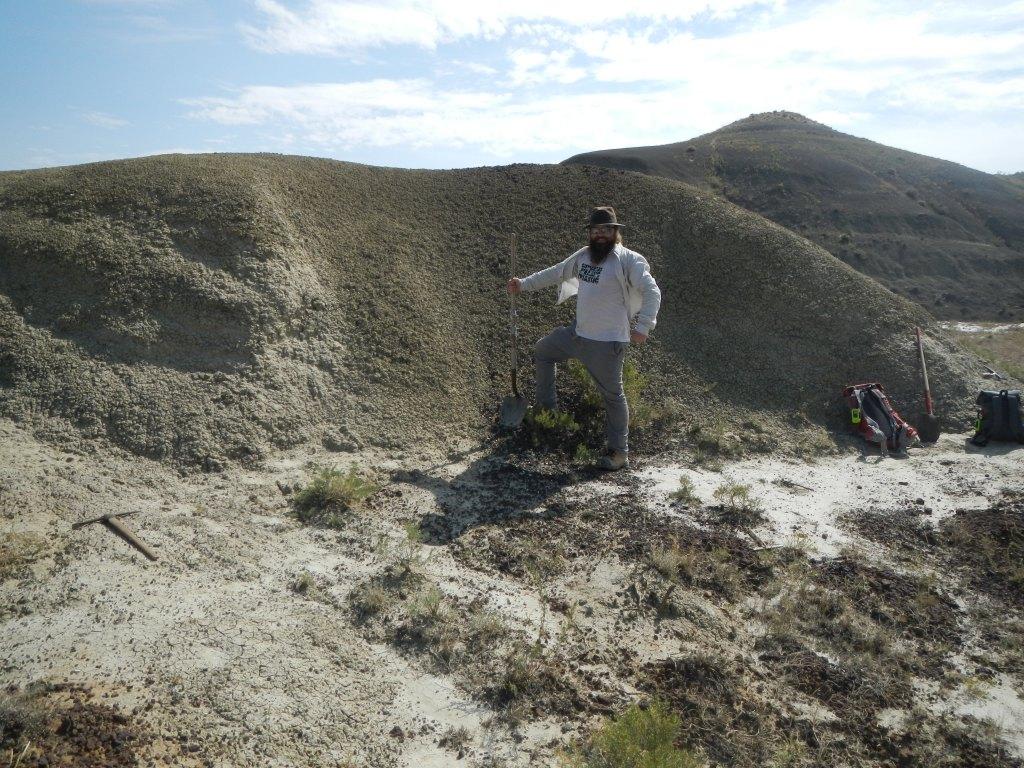 Un homme muni d'une pelle, debout devant un petit tas de terre.