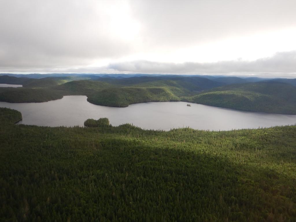 Photo d'un grand lac entouré de toutes parts par une forêt dense. Il y a des nuages dans le ciel, mais la lumière du soleil éclaire les collines boisées.