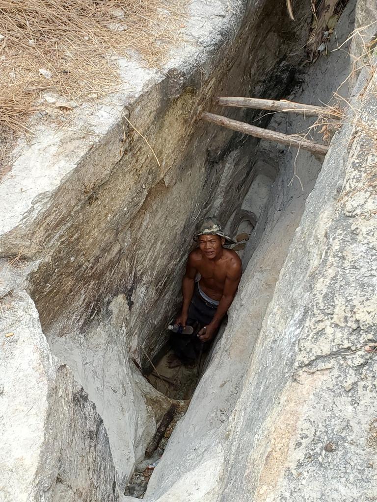 Un mineur travaille dans une tranchée à l'extraction de fluorite d'une veine.