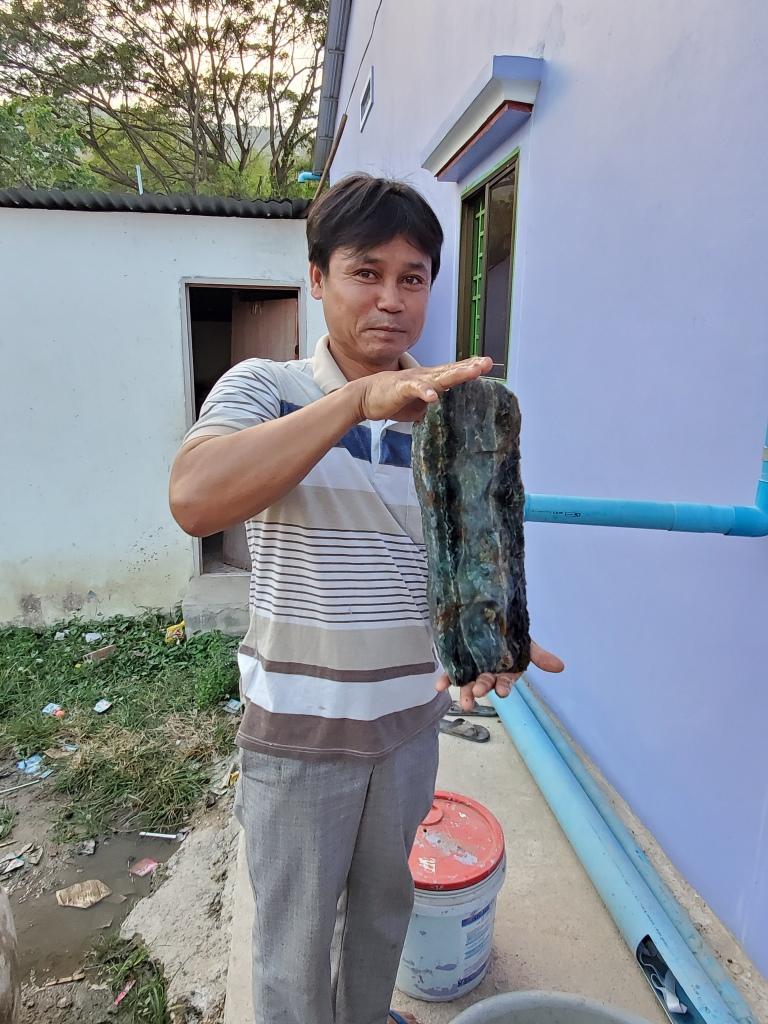 M. Sokphun tient un gros morceau de fluorite verte et violette extrait de sa mine.
